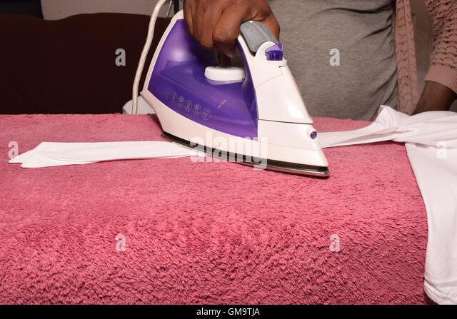 House wife Ironing White Shirt - Stock Image