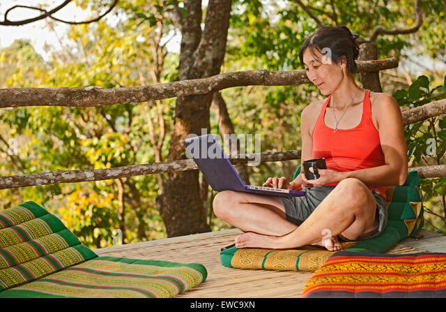 Woman sitting with her laptop on an outdoor terrase at a street cafe in northern Thailand - Stock Image