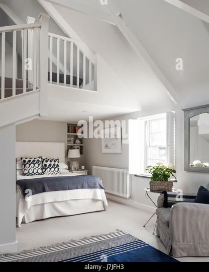 Bright and spacious mezzanine bedroom. The armchair is covered in Ian Mankin's Ticking 01 fabric and the welsh - Stock Image