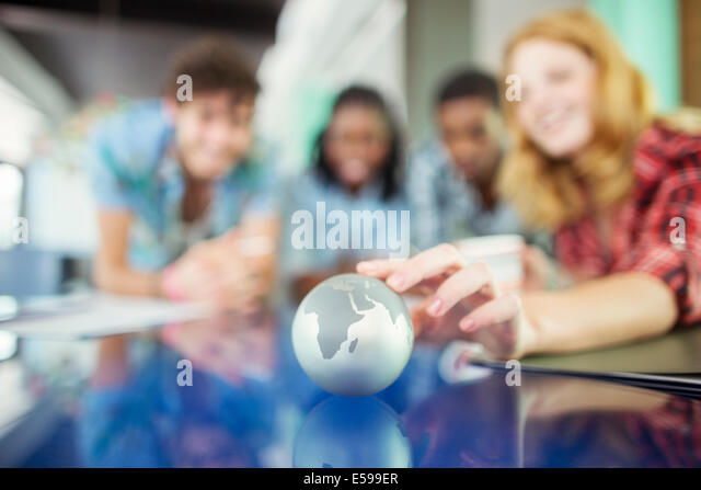 People examining miniature globe - Stock Image