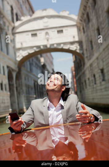 Enthusiastic businessman riding on boat through canal in Venice - Stock Image