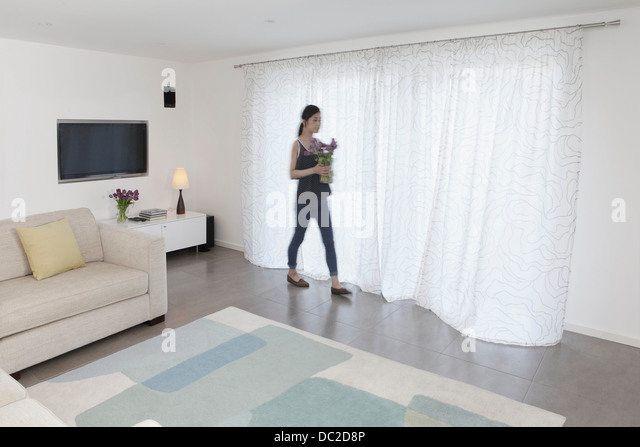 Woman with vase of flowers walking past curtains - Stock-Bilder