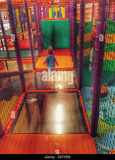 Toddler playing in indoor playground m - Stock Image