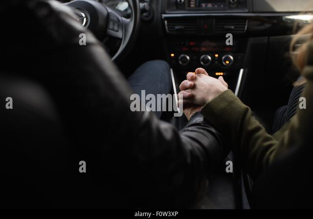 Couple holding hands inside vehicle - Stock-Bilder
