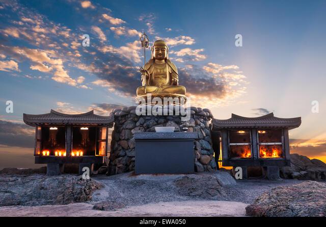 The sun rises behind a Buddha statue at Haedong Yonggungsa Temple in Busan, South Korea. - Stock Image