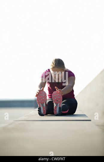 Runner stretching on rooftop - Stock Image