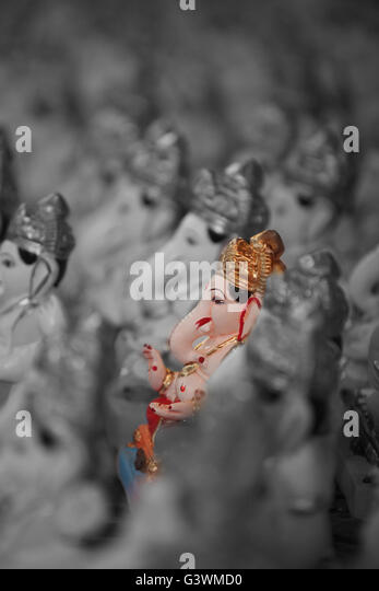 A metaphorical image showing a selected colorful lord Ganesha idol amongst many. - Stock Image