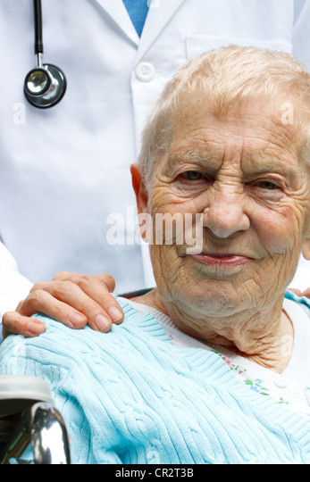 Senior Woman in Wheelchair with Doctor behind her - Stock Image