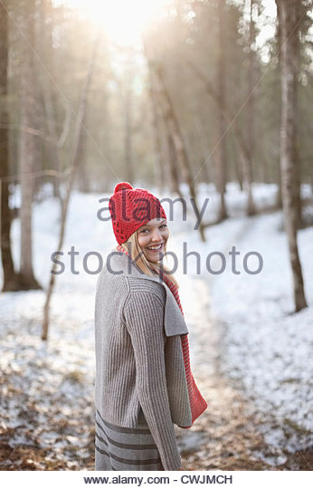 Portrait of smiling woman walking in snowy woods - Stock Image