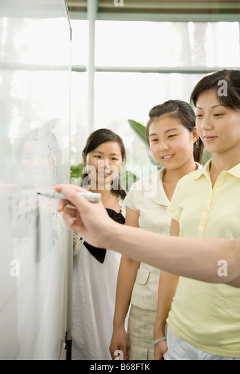 Close-up of a person's hand writing on a whiteboard with three female office workers looking on it - Stock Image