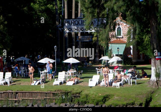 People sunbathe at a rowing club along the Parana Delta at Tigre, Argentina. - Stock Image
