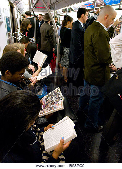 Passengers reading  on New York Subway train - Stock Image