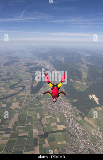 Female skydiver free falling upside down over Grenchen, Berne, Switzerland - Stock-Bilder