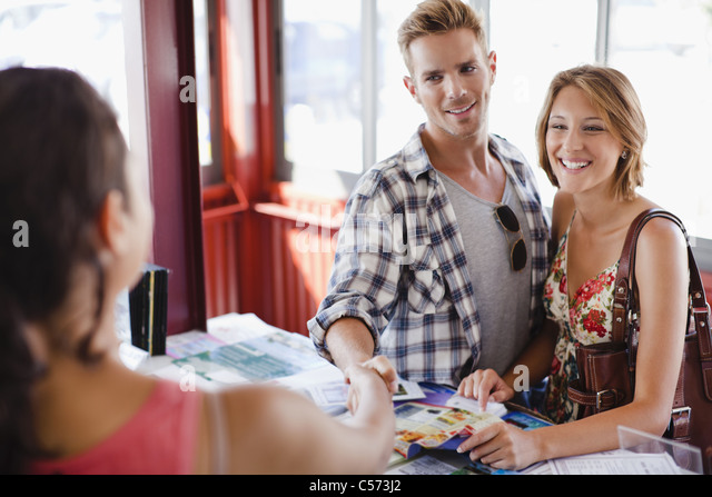 Smiling couple at tourist info center - Stock Image