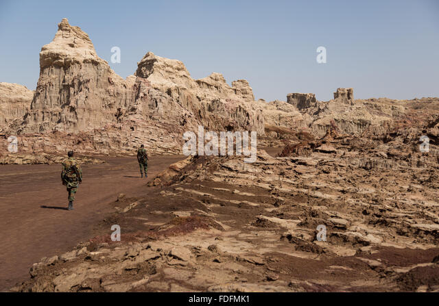 Armed guards stroll through the moonscape of salt deposits near the salt volcano at Dallol, Ethiopia - Stock Image