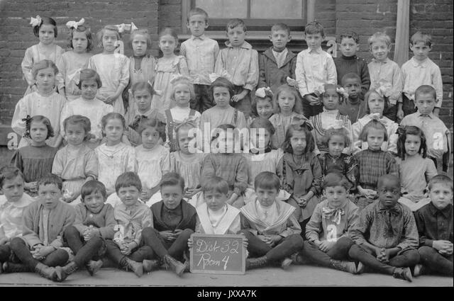 Full length landscape shot of schoolchildren, all seated except back row, one African American boy in the front - Stock Image
