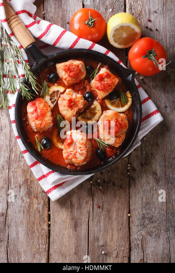 Pieces of fish in tomato sauce with olives and lemon in a frying pan. vertical top view - Stock Image