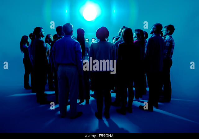 Crowd standing around bright light - Stock Image