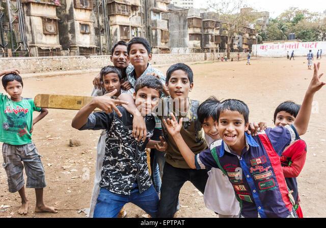 Mumbai India Asian Dharavi Shahu Nagar Road slum dirt lot cricket field pitch boy friends playing bat hand signals - Stock Image
