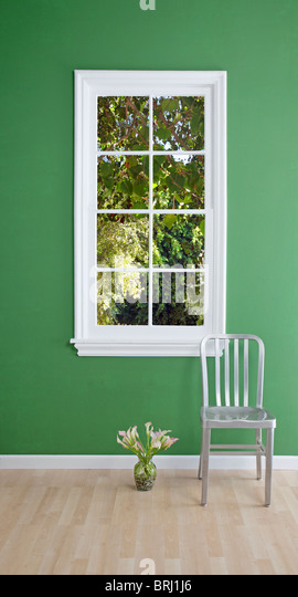 chair and flowers by the window - Stock Image