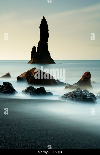 Waves washing in around black volcanic sea stacks on the Vik coast in Iceland - Stock Image