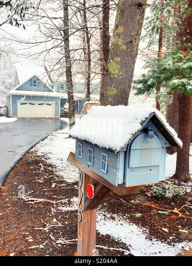 Scenic winter scene suburban new England luxury home in mailbox after snowstorm, USA - Stock Image