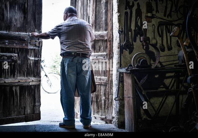 Rear view of senior male blacksmith in opening doors of traditional barn, Cagliari, Sardinia, Italy - Stock-Bilder