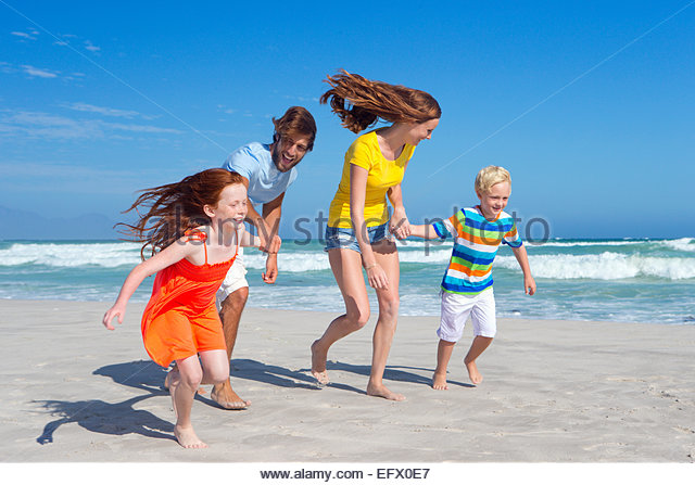 Happy family holding hands, running along sunny beach - Stock-Bilder
