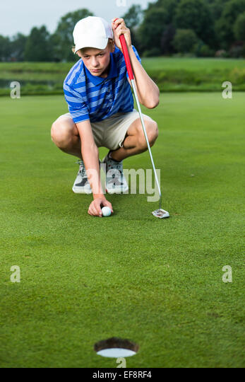 Teenage boy placing ball on tee on golf course - Stock Image