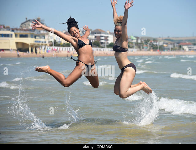 Weymouth, UK. 19th July, 2016. Georgia Gilling, left and Kaysha Brown enjoy the hottest day with temperatures in - Stock Image