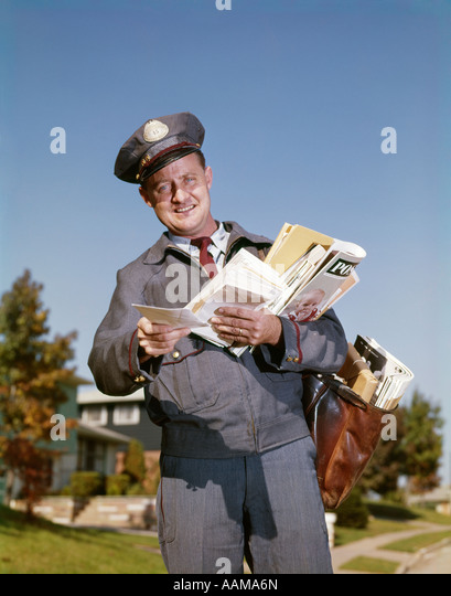 1960s SMILING MAILMAN HODLING LETTERS MAIL MAILBAG - Stock Image