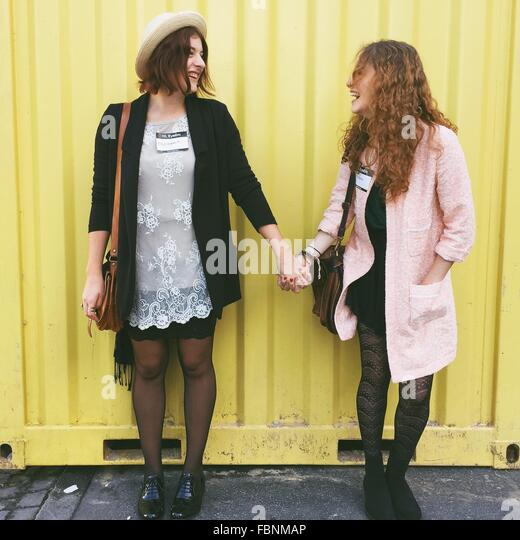Cheerful Friend Holding Hands While Standing Against Metal Wall - Stock Image