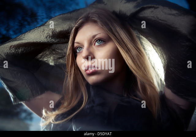 Woman with green scarf sunlight behind her - Stock Image