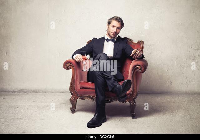Gentleman sitting on a vintage armchair - Stock Image