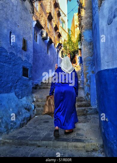 Woman ascending the stairs in Chefchaouen, Morocco - Stock Image