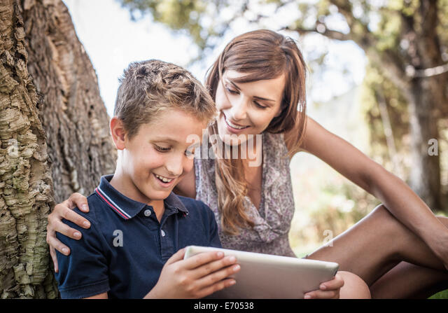 Mother and son looking at digital tablet in holiday home garden, Capoterra, Sardinia, Italy - Stock-Bilder
