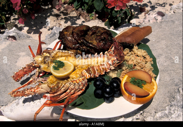 Caribbean food portrait lobster barbecue bbq chicken lunch plate Anguilla Scilly Cay - Stock Image