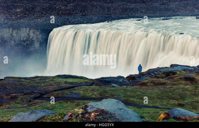 Tourist admiring view of falling water of the most powerful waterfall in Europe - Dettifoss. Jokulsargljufur National - Stock Image