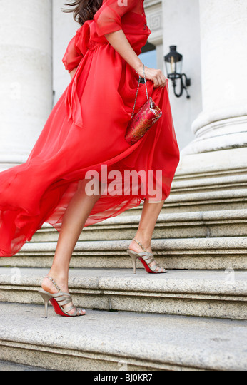 detail of young woman in red dress running up stairs of theatre - Stock Image
