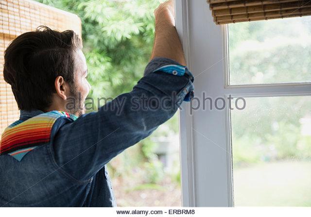 Brunette man looking out doorway - Stock-Bilder