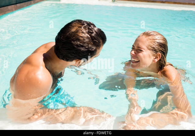 Happy couple laughing in the pool - Stock Image