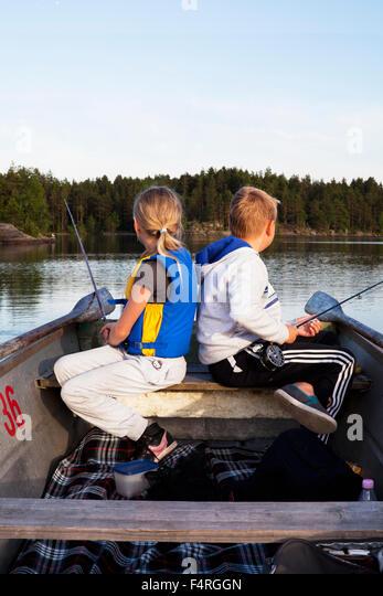 Girl and boy (8-9, 10-11) fishing on lake - Stock Image