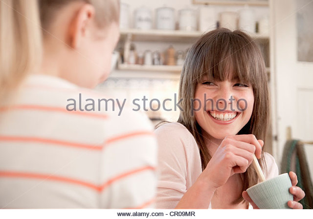 Smiling mother with child in kitchen - Stock Image