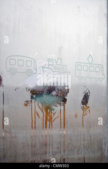 Drawings on condensate window glass - Stock-Bilder