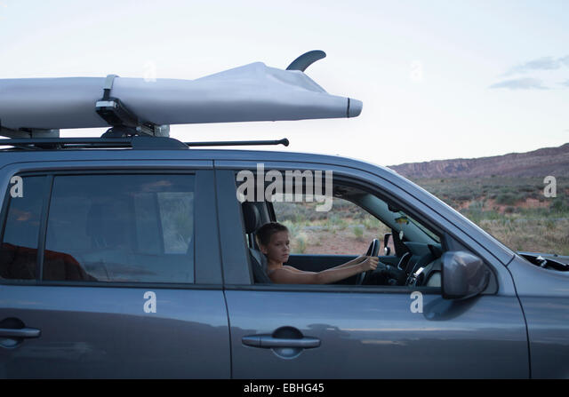 Teenage boy in driver seat of recreational vehicle, Arches National Park, Moab, Utah, USA - Stock Image