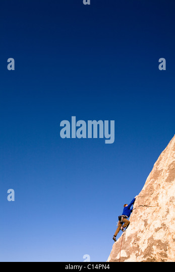 A climber in a blue jacket reaches for a handhold while climbing the Southwest Corner of Headstone Rock in Joshua - Stock Image