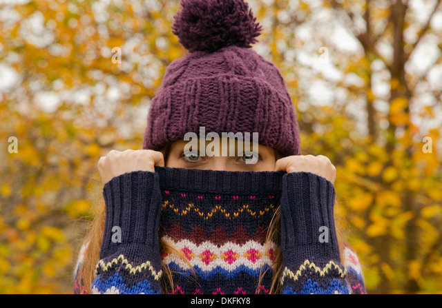 Close up portrait of young woman in park with jumper hiding face - Stock Image