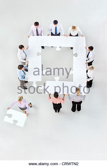 Businesswoman removing jigsaw piece from square formed by business people - Stock Image