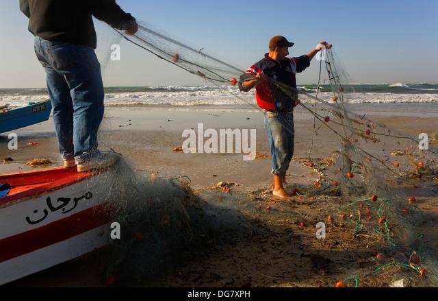 Tunez:Hammamet. Beach.Fishermen checking a net - Stock Image