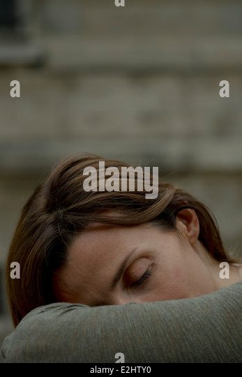 Woman resting head on arms - Stock Image